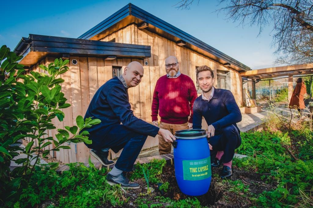 Three men with a blue plastic barrel in front of a single storey wooden building