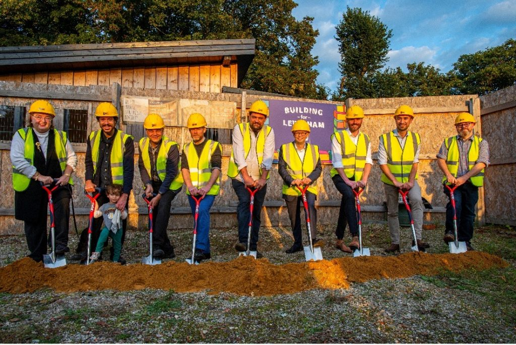 Nine people in yellow hard hats and hi-vis vests digging into soil with spades. In the background, a hoarding and the roof of the RUSS Community Hub.